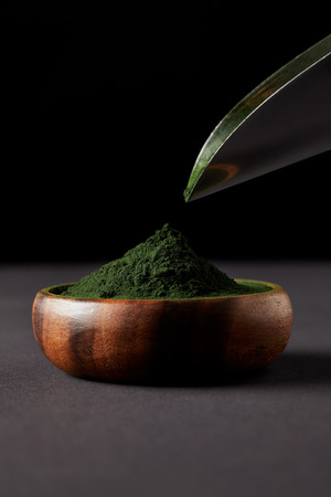 selective focus of scoop over spirulina powder in wooden bowl on black background