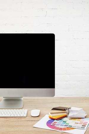 close-up van designer werkruimte met pallet, leeg computerscherm en toetsenbord op houten oppervlak Stockfoto