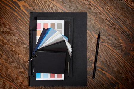 flat lay with black notebooks, colors pallet and pencil on wooden tabletop Stock Photo