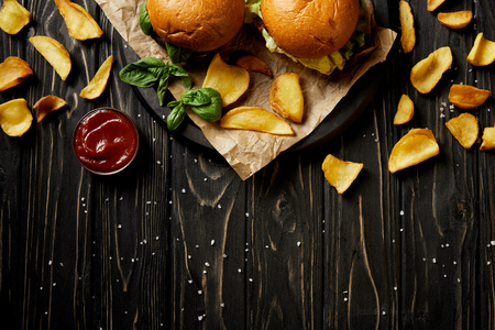 Top view of tempting hamburgers and fried potatoes on wooden table
