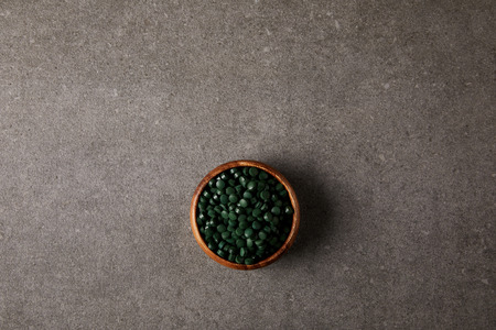 top view of wooden bowl with pile of spirulina pills on stone table Фото со стока