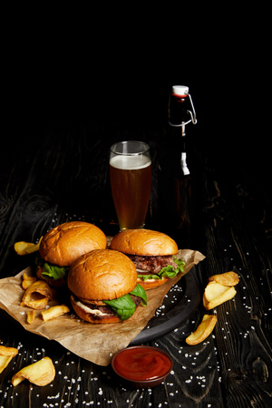 Hamburgers and french fries on table with beer in bottle and glass Stock Photo