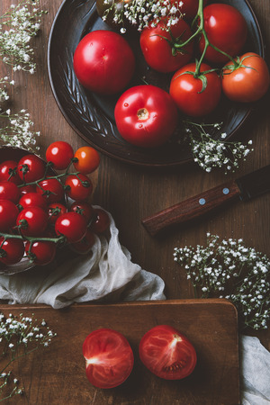 top view of fresh tomatoes on ceramic plate and cutting board with knife