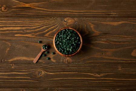 top view of wooden spoon and bowl with pile of spirulina pills on wooden table