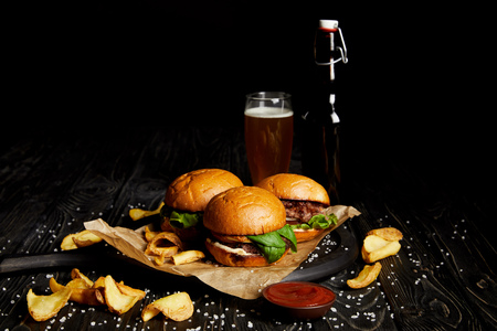 Set of junk food with burgers and french fries on table with beer in bottle and glass