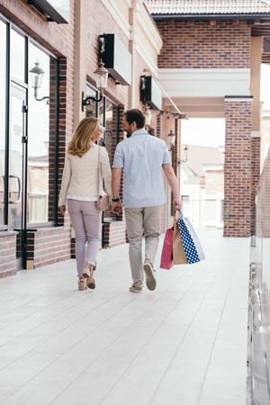 back view of couple holding hands and walking with shopping bags