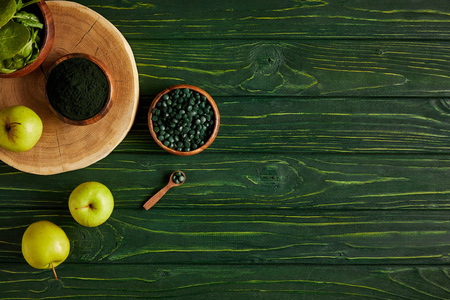top view of cutting board, wooden bowls, spoon, apples, leaves, spirulina powder and spirulina pills on green wooden table