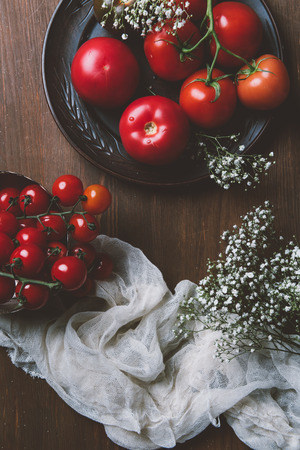 top view of red fresh tomatoes in ceramic plate on wooden background with flowers and gauze