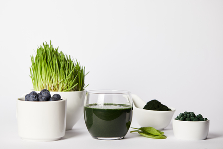 fresh smoothie from spirulina, cups with spirulina grass and blueberries, leaves, bowls with spirulina powder and spirulina pills on grey background