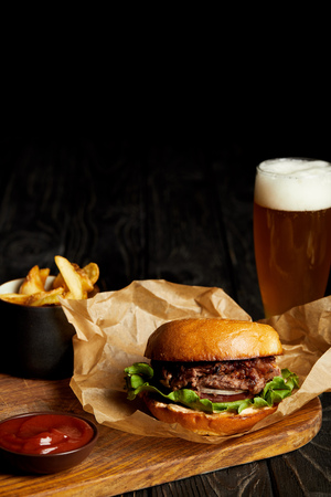 Hamburger and french fries served with cold beer in glass