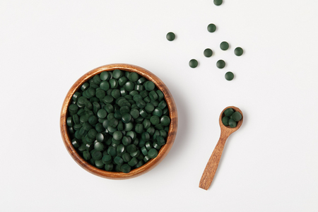 elevated view of wooden spoon and bowl with pile of spirulina pills on grey table