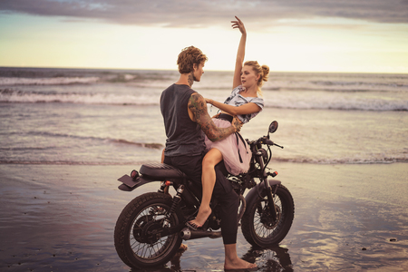 young couple hugging on motorcycle on ocean beach during beautiful sunrise Archivio Fotografico - 105907965