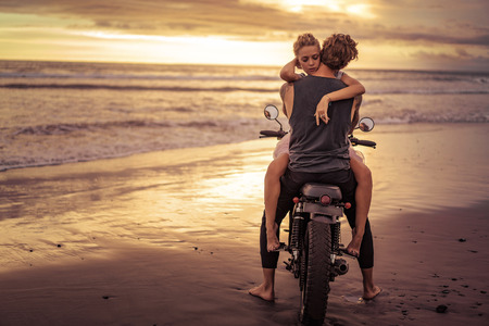 couple hugging on motorcycle on ocean beach during beautiful sunrise