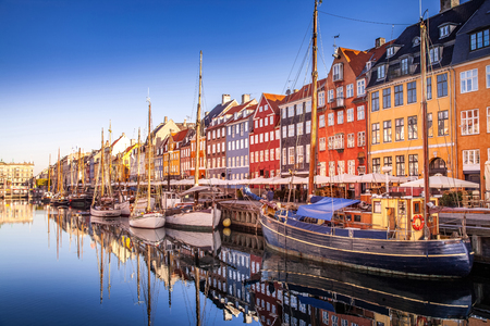 COPENHAGEN, DENMARK - MAY 6, 2018: picturesque view of historical buildings and moored boats reflected in calm water, copenhagen, denmark Редакционное