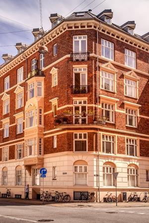 COPENHAGEN, DENMARK - MAY 6, 2018: man walking on street and bicycles standing near building in Copenhagen, Denmark