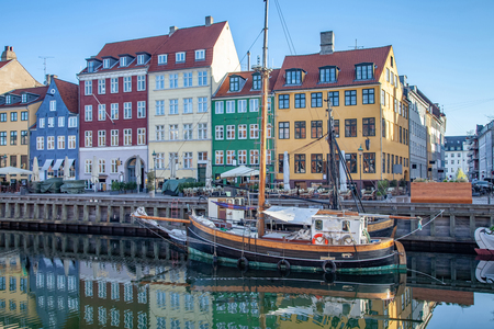 COPENHAGEN, DENMARK - MAY 6, 2018: boat and beautiful colorful buildings reflected in calm water of harbor, copenhagen, denmark Редакционное