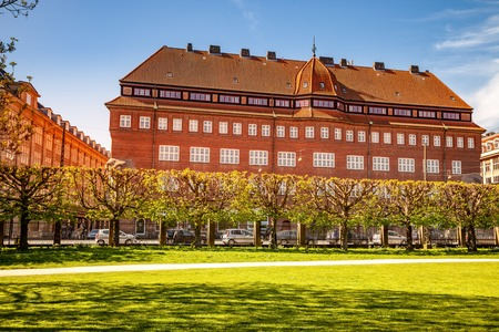 COPENHAGEN, DENMARK - MAY 6, 2018: scenic view of green lawn in park and cars on parking lot in front of building Editorial