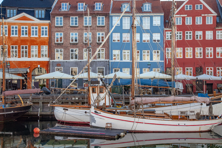 COPENHAGEN, DENMARK - MAY 6, 2018: beautiful colorful buildings and boats moored in harbor, copenhagen, denmark Редакционное