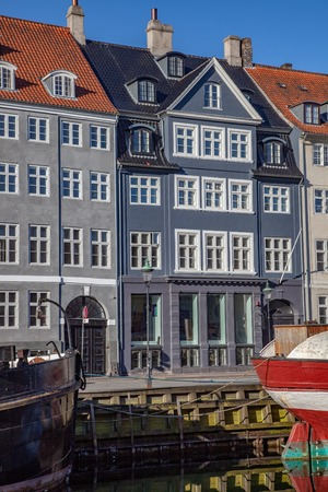 COPENHAGEN, DENMARK - MAY 6, 2018: beautiful historical buildings near water and moored boats in copenhagen, denmark Редакционное