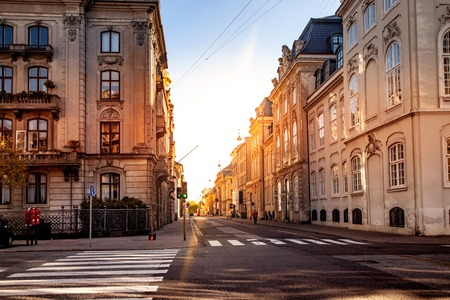 COPENHAGEN, DENMARK - MAY 6, 2018: scenic view of cityscape with buildings and street with sunlight