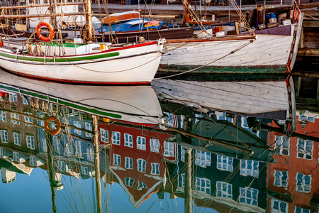 COPENHAGEN, DENMARK - MAY 6, 2018: historical buildings and boats reflected in calm water, copenhagen, denmark Редакционное