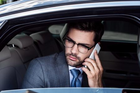 portrait of businessman talking on smartphone on backseat in car Stock fotó