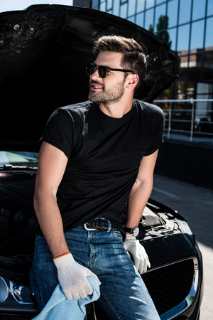 smiling young man in working gloves holding rug near broken car with opened bonnet