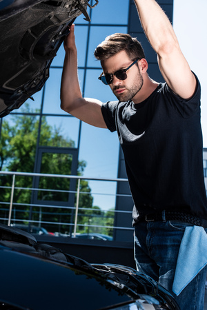 low angle view of young man in sunglasses checking car engine at street