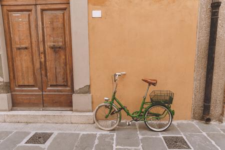 green retro bike standing near old orange wall, Pisa, Italy