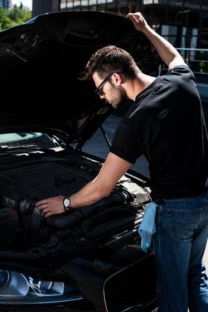 focused young man looking under car hood of breakdown car at street