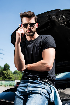 young stylish man in sunglasses smoking cigarette near broken car with opened bonnet 스톡 콘텐츠