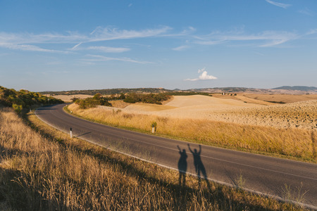 scenic view of beautiful Tuscany fields, empty road and peoples shadow, Italy Stock Photo