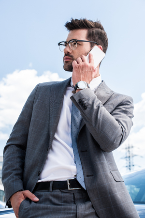 businessman in eyeglasses talking on smartphone while standing near car on street