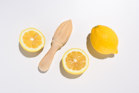 top view of lemons and wooden squeezer on white surface