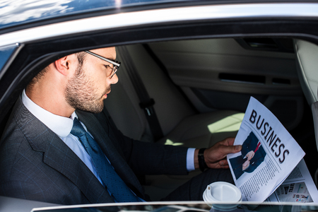 side view of businessman with coffee to go reading newspaper on backseat in car