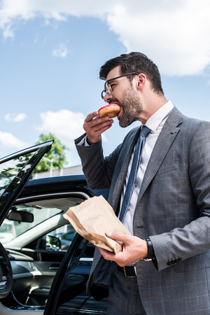 side view of businessman eating take away doughnut while standing at car on street Imagens