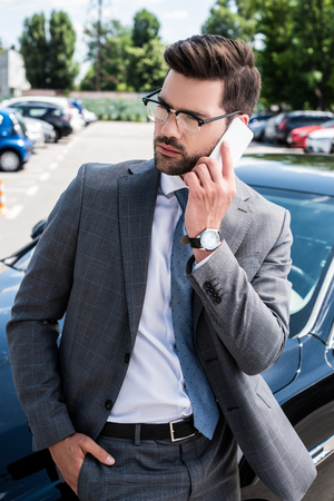 portrait of businessman in eyeglasses talking on smartphone while standing near car on street Stock fotó