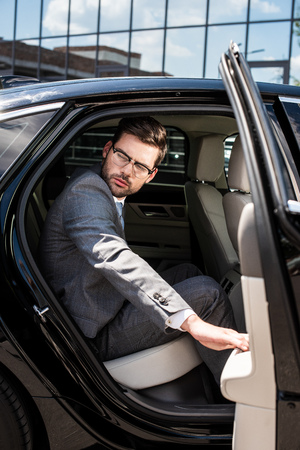 side view of pensive businessman looking away while sitting on backseat with opened car door
