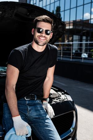 smiling man in working gloves holding rag near car with opened bonnet at street Reklamní fotografie