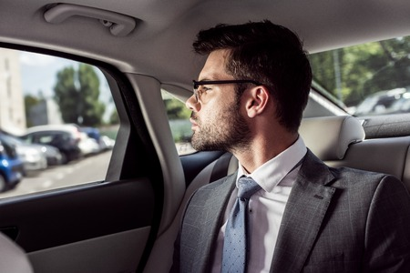 portrait of pensive businessman in eyeglasses looking out car window while sitting on backseat in car Stock Photo