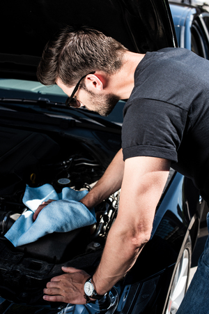 side view of young man in sunglasses checking car engine at street