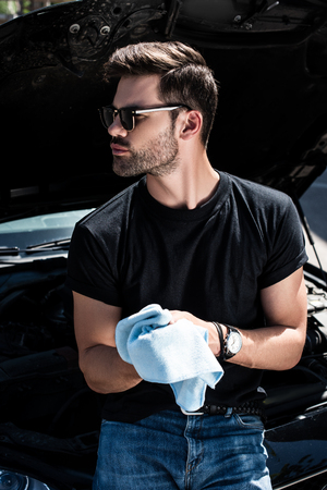 young man in sunglasses wiping hands by rag near car with opened bonnet