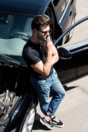 high angle view of stylish man in sunglasses closing mouth by fingers near broken car with opened bonnet