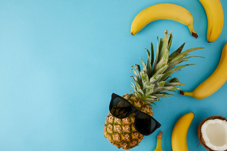 top view of fresh coconut, bananas and pineapple with sunglasses isolated on blue
