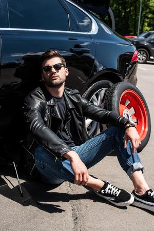 tired stylish man in sunglasses sitting near broken car at street Stock Photo