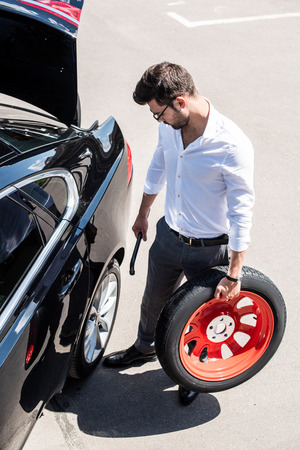 high angle view of young businessman in eyeglasses holding wheel spanner and tire near car at street Stok Fotoğraf