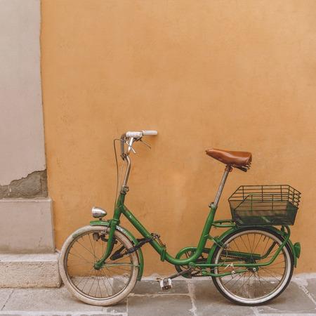 vintage green bicycle standing near orange wall, Pisa, Italy