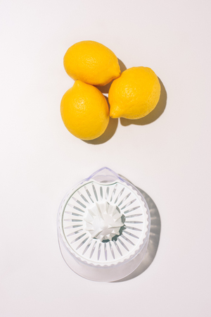 top view of juicer and lemons on white table Stock Photo