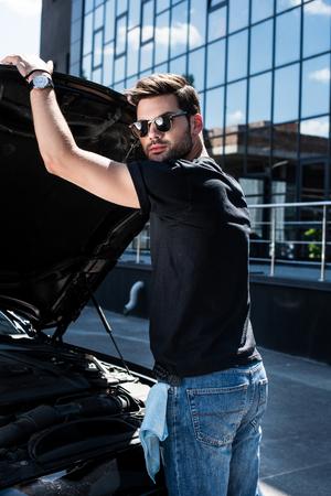 stylish man in sunglasses closing bonnet of car at street Stock Photo