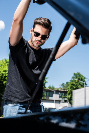 low angle view of young man in sunglasses opening bonnet at street